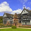 Black and white timber framed medieval mansion house and gardens. — Stock Photo #54152693