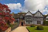 Black and white timber framed medieval mansion house and gardens. — Stock Photo