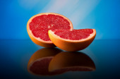 Grapefruit on a bright abstract background with reflection — Stok fotoğraf