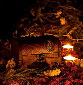 Magic chest on dry grasses by candlelight — Stock Photo