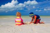 Brother and sister playing with sand on beach — Stock Photo