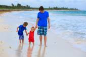 Père et deux enfants marchant sur la plage — Photo