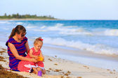 Mother and little daughter on tropical beach — Stock Photo