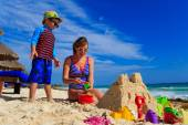 Mother and son building sand castle on tropical beach — Foto de Stock