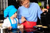 Father and son preparing waffles in kitchen — Stock Photo