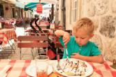 Lille pojken äta i staden café sommardag — Stockfoto