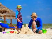 Father and son building sand castle on the beach — Stock Photo