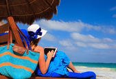 Woman with touch pad on tropical beach — Stock Photo