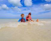 Mother with kids splasing water at the sea — Stock Photo