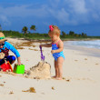 Little boy and toddler girl playing with sand on the beach — Stock Photo #69309825