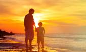 Father and son holding hands at sunset sea — Stock Photo