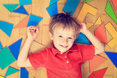 Happy little boy with puzzle toys on wooden floor — Stock Photo