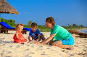 Father and two kids playing with sand on the beach — Stock Photo