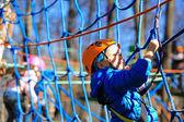Little boy climbing in adventure activity park — Стоковое фото
