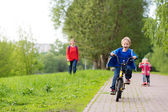 Happy kids riding scooter and bike in the park — Stock Photo