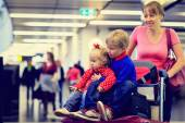 Mother with two kids travel in the airport — Stock Photo