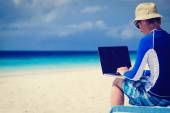 Man with laptop on beach vacation — Stock Photo