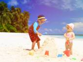 Little boy and toddler girl building sandcastle on beach — Stock Photo