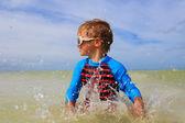Niño jugando con agua en la playa tropical — Foto de Stock