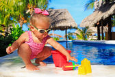 Little girl playing in swimming pool at tropical beach — Stock Photo