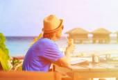 Muž pít koktejl při pohledu na podložce v tropických resort — Stock fotografie
