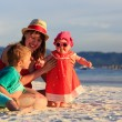 Mother and kids having fun on sand beach — Stock Photo #83200840