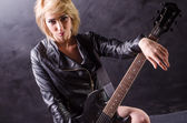 Beautiful young blonde dressed in black leather jacket with electric guitar on a black background — Stock Photo