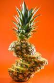Artistic sliced, standing pineapple on orange background, vertical shot — Stock Photo