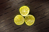 Slice of lemon or lime on black background with stripes — Stock Photo