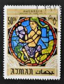 AJMAN - CIRCA 1971: A stamp printed in Ajman shows the horoscope sign of Aquarius, series is devoted to the frescoes in the cathedral of Notre Dame, circa 1971 — Stock Photo