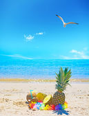 Pineapples and coconuts by the shore — Stock Photo