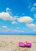 Růžové žabky na písku v Sardinii — Stock fotografie
