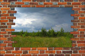 Broken brick wall and view to field with thunder storm clouds — ストック写真