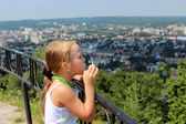 Little girl swelling soap bubbles out of city — Stockfoto