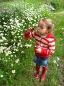 Little girl swelling soap bubbles in flower-bed — Stockfoto