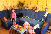 маленькая девочка с игрушками в ее комнате — Стоковое фото