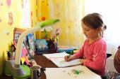 Garota do colegial aprende lições na mesa — Fotografia Stock