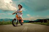 Child on orange bicycle — Stock Photo