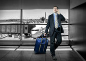 Businessman with baggage in airport — Stock Photo