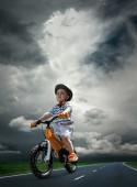 Child on the orange bicycle — Stock Photo