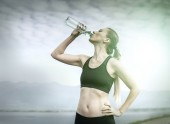 Female drinks water after running — Stock Photo