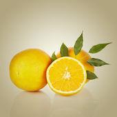 Sliced orange fruit with leaves — Stock Photo