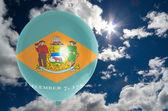 Globo con la bandera de delaware en el cielo — Foto de Stock