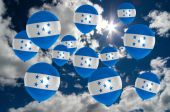 Many balloons with honduras flag on sky — Stock Photo
