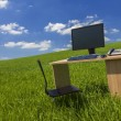 Desk and Computer In Green Field With Blue SKy — Stock Photo #53973721
