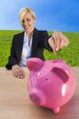 Woman Putting Money into Pink Piggy Bank — Stock Photo