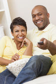 Couple in their thirties watching television — Stockfoto