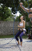 Asian Woman in belaying stance in outdoor rockclimb — Stock Photo