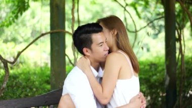 Asian couple whispering in a park — Stock Video