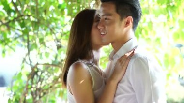 Asian couple holding each other closely in a park — Stock Video